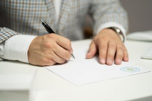 A man signing a contract after negotiating a commercial lease.